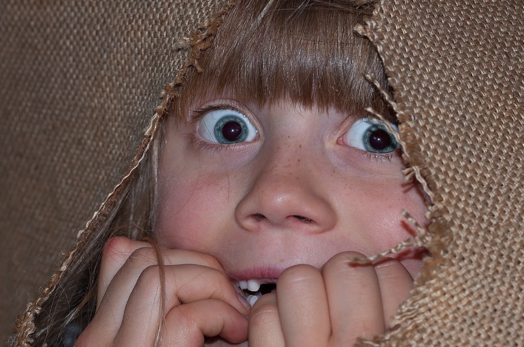 image of girl looking scared and hiding under a sheet