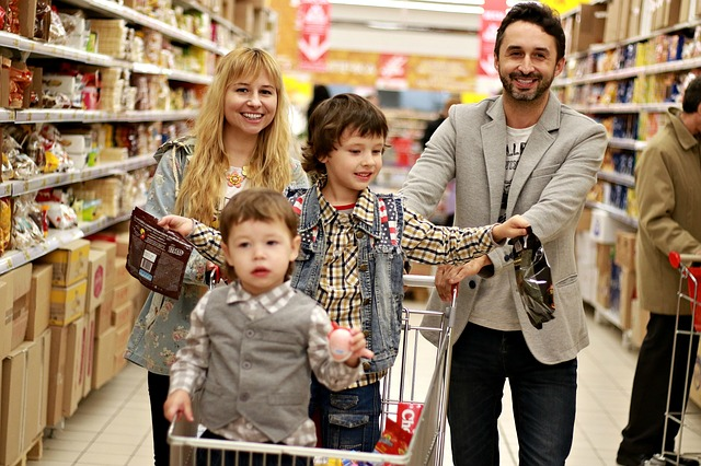 Picture of husband, wife and two kids at the grocery store shopping for food